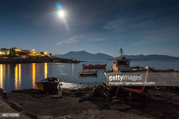 scenic view of boats by coast at night - vgenopoulos stock pictures, royalty-free photos & images