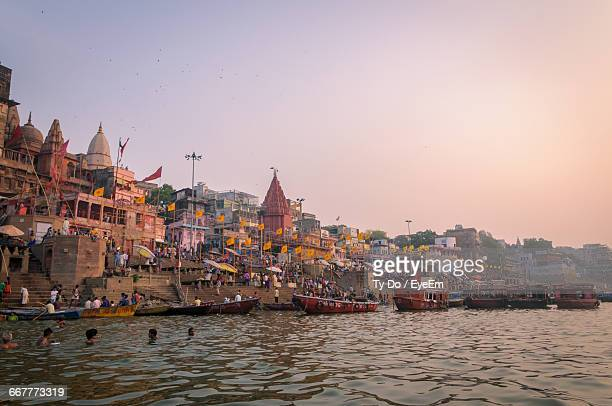 Scenic View Of Boats In River Next To Temple Against Clear Sky