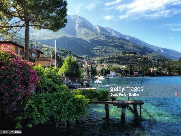 scenic view of building and mountains against sky - malcesine stock pictures, royalty-free photos & images
