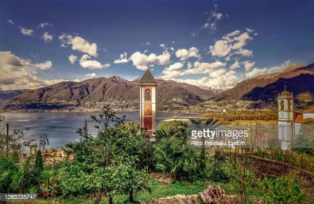 scenic view of building by mountains against sky - ascona stock pictures, royalty-free photos & images