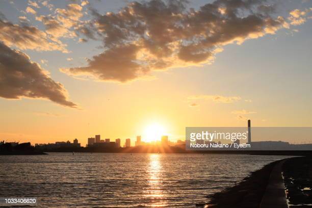 scenic view of buildings against sky during sunset - 日没 ストックフォトと画像