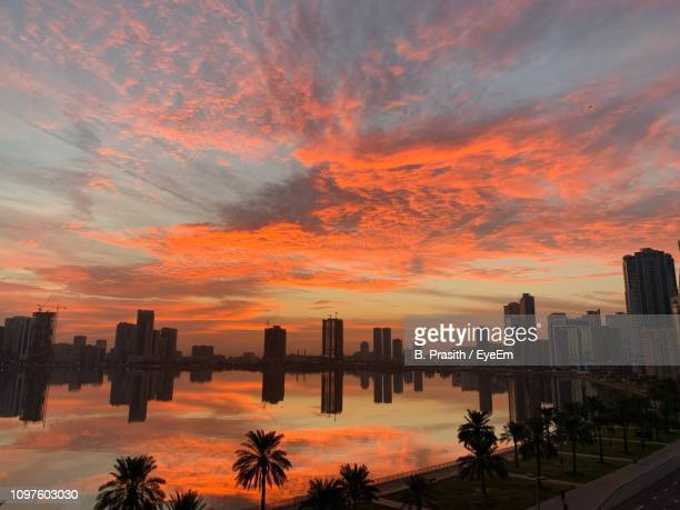 scenic view of buildings against sky during sunset - emirate of sharjah stock pictures, royalty-free photos & images