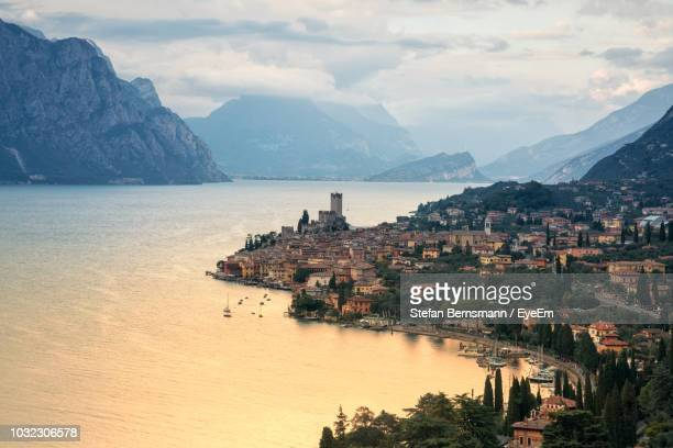 scenic view of buildings by sea against cloudy sky - malcesine stock pictures, royalty-free photos & images