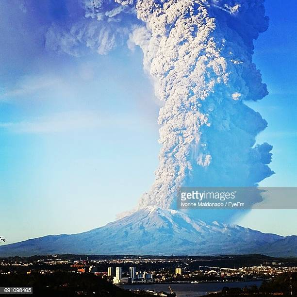 scenic view of calbuco volcano erupting against blue sky - calbuco volcano stock pictures, royalty-free photos & images