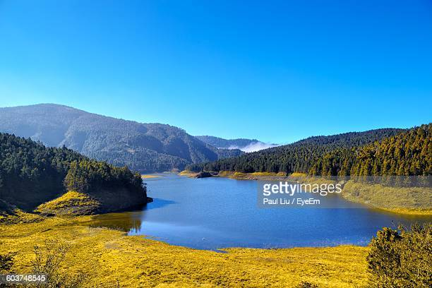 scenic view of calm lake against clear blue sky - liu he stock pictures, royalty-free photos & images