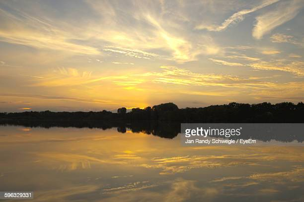 Scenic View Of Calm Lake Against Cloudy Sky During Sunset