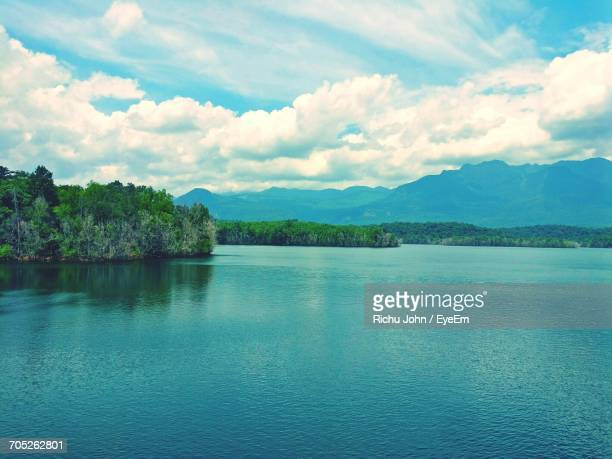 scenic view of calm lake against cloudy sky - thiruvananthapuram stock photos and pictures