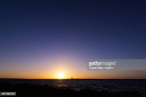 Scenic View Of Calm Sea Against Clear Sky At Sunset