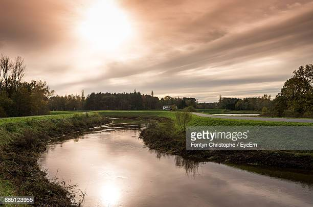 scenic view of canal along the road against cloudy sky - moody sky stock pictures, royalty-free photos & images