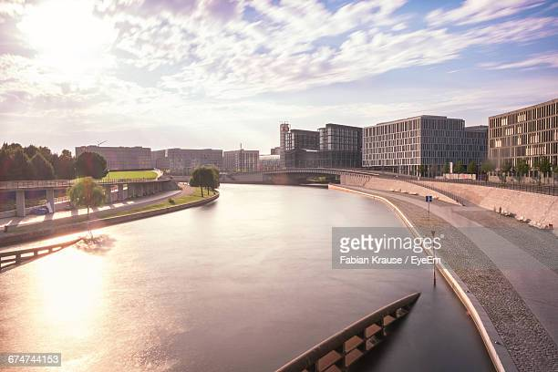 Scenic View Of Canal In City Against Cloudy Sky
