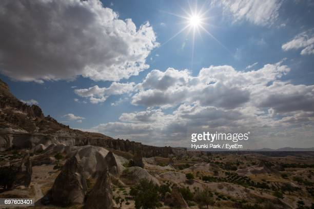 scenic view of cappadocia against cloudy sky on sunny day - central anatolia stock photos and pictures