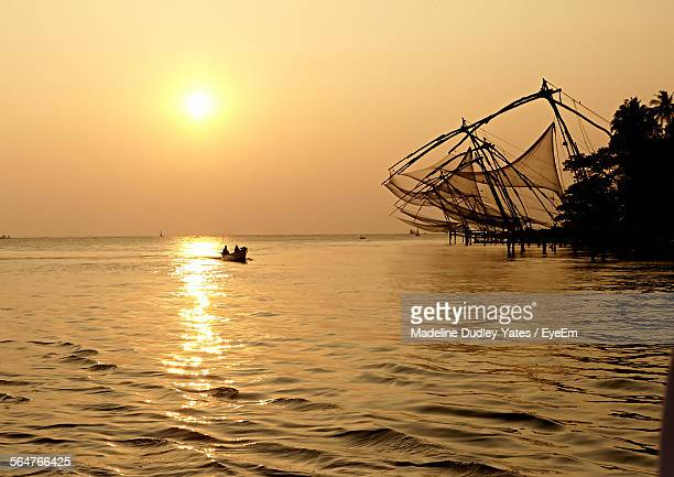 Scenic View Of Chinese Fishing Net In Sea At Sunset