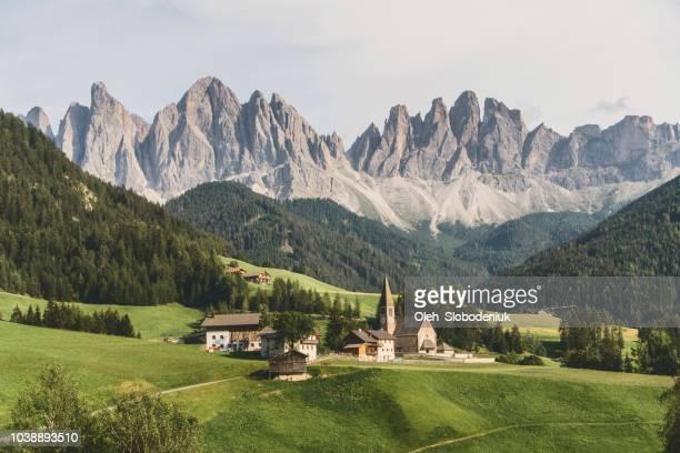 scenic view of church  in dolomites alps - cittadina foto e immagini stock