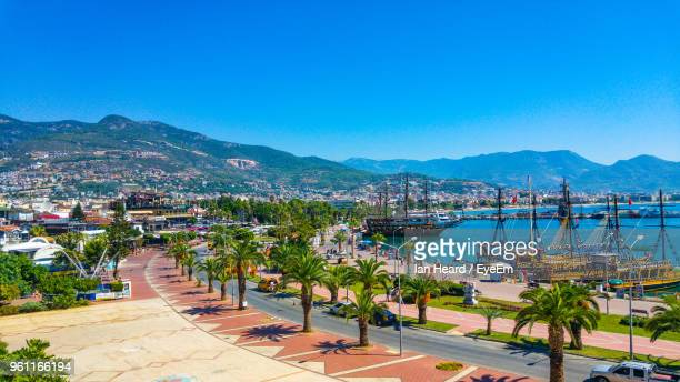 scenic view of city by sea against clear blue sky - antalya stock-fotos und bilder