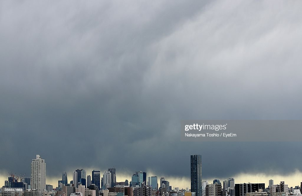 Scenic View Of Cityscape Against Cloudy Sky : Stock Photo