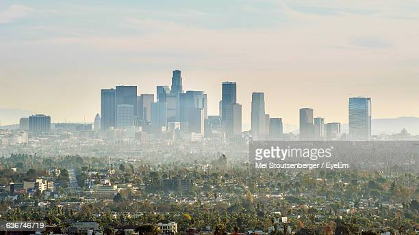Scenic View Of Cityscape Against Sky In Foggy Weather
