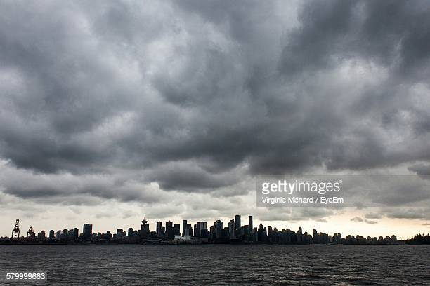 Scenic View Of Cityscape And Sea Against Cloudy Sky