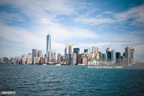 Scenic View Of Cityscape By Sea Against Sky