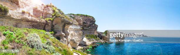 Scenic View Of Cliff By Sea Against Clear Blue Sky