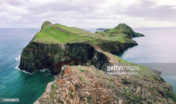 scenic view of cliff by sea against sky - madeira island stock photos and pictures