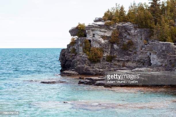 scenic view of cliff by sea against sky - barrie stock pictures, royalty-free photos & images