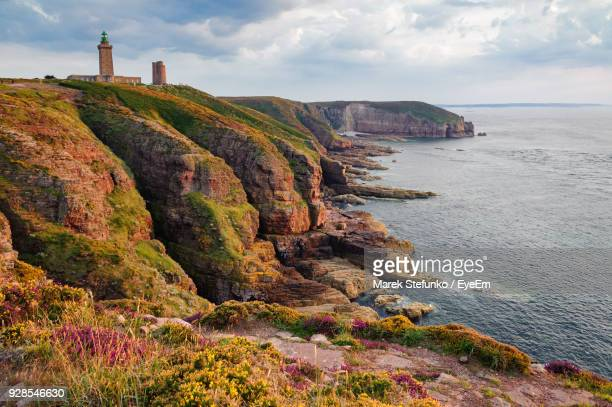 scenic view of cliff by sea against sky - marek stefunko stock photos and pictures