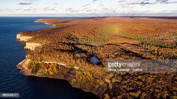 scenic view of cliff by sea during autumn - munising michigan stock pictures, royalty-free photos & images