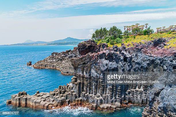 scenic view of cliffs by sea against sky - jeju stock photos and pictures