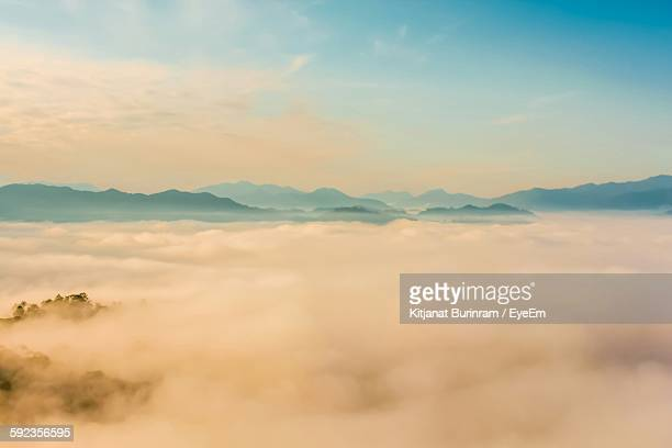 Scenic View Of Clouds Covered Mountains During Sunset