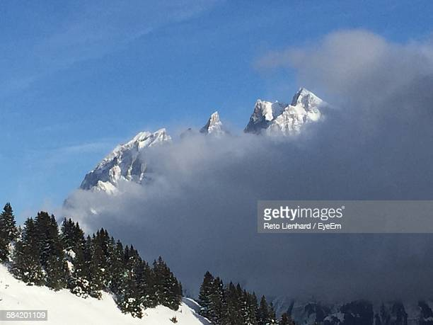 scenic view of clouds touching snow covered mountains - lienhard stock pictures, royalty-free photos & images