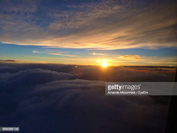 Scenic View Of Cloudscape Seen From Airplane Window During Sunrise