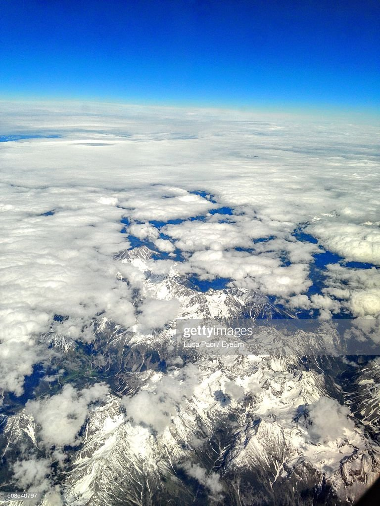 Scenic View Of Cloudy Sky Over Snow Covered Mountains : Stock Photo