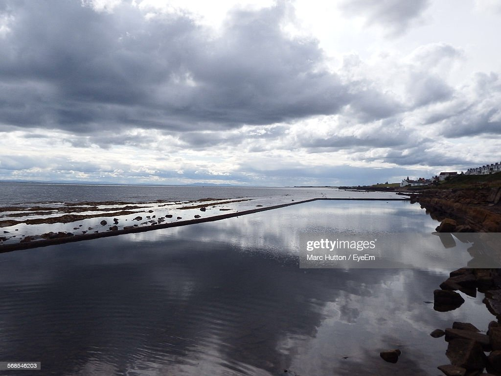 Scenic View Of Cloudy Sky Reflected In Infinity Pool : Stock Photo