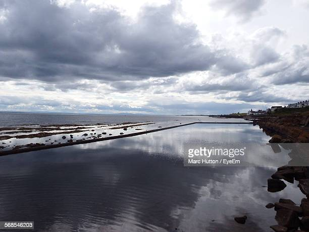 scenic view of cloudy sky reflected in infinity pool - hutton stock photos and pictures