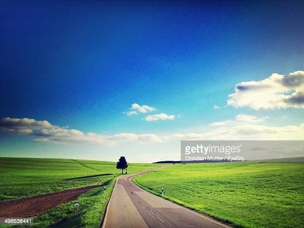 Scenic view of country road and green fields