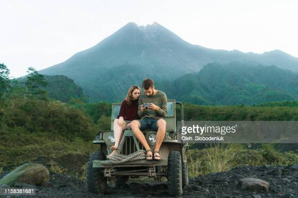 Scenic view of couple sitting on old fashioned SUV on the background of Merapi volcano