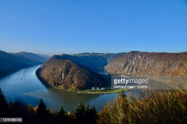 scenic view of curved river and mountains against clear blue sky - gerhard hagn stock-fotos und bilder