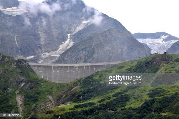 scenic view of dam and mountains against sky - gerhard hagn stock-fotos und bilder