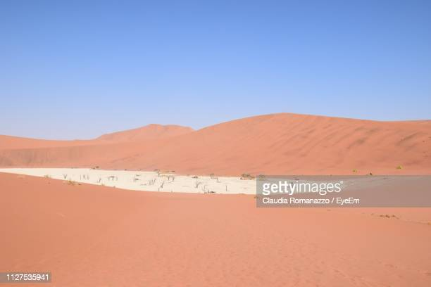 scenic view of desert against clear blue sky - claudia romanazzo foto e immagini stock