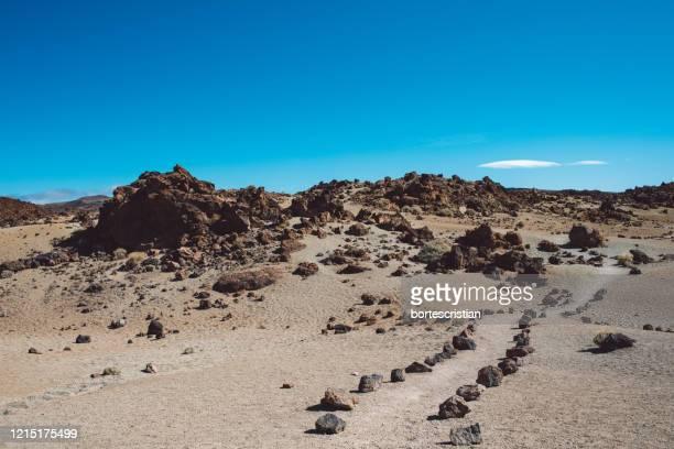 scenic view of desert against clear blue sky - bortes stock-fotos und bilder