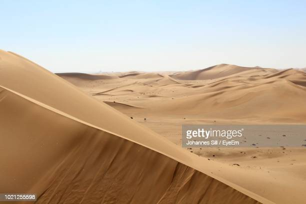 scenic view of desert against clear sky - walvis bay stock photos and pictures