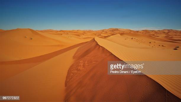 scenic view of desert against clear sky - merzouga stock pictures, royalty-free photos & images