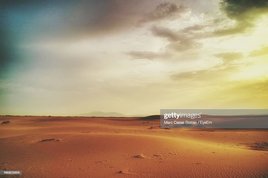 Scenic View Of Desert Against Cloudy Sky During Sunset : Foto de stock
