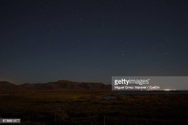 Scenic View Of Desert And Distant Town At Night