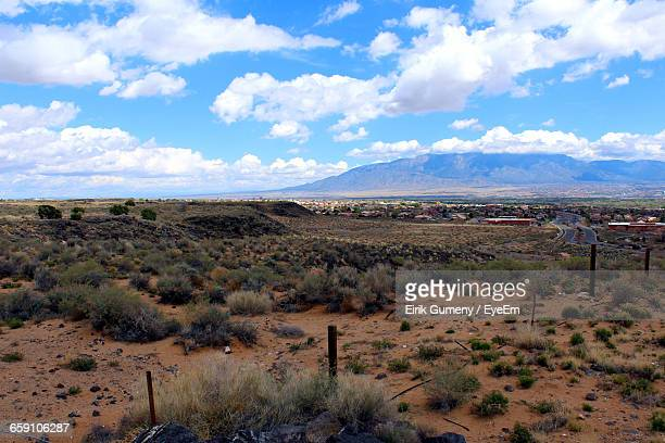 Scenic View Of Desert Landscape Against Cloudy Sky