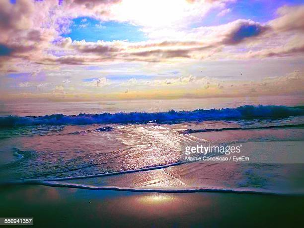 Scenic View Of Dramatic Sky Over Beach At Sunset