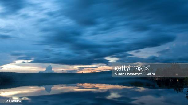 scenic view of dramatic sky over lake during sunset - thai mueang photos et images de collection