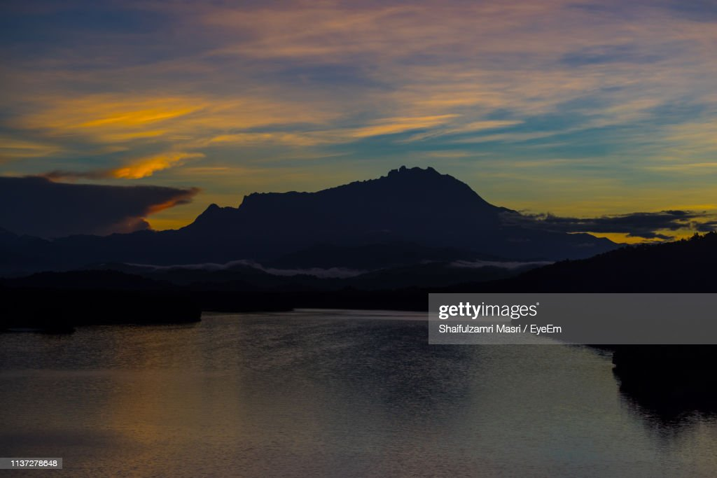 Scenic View Of Dramatic Sky Over Mountains During Sunset : Stock Photo