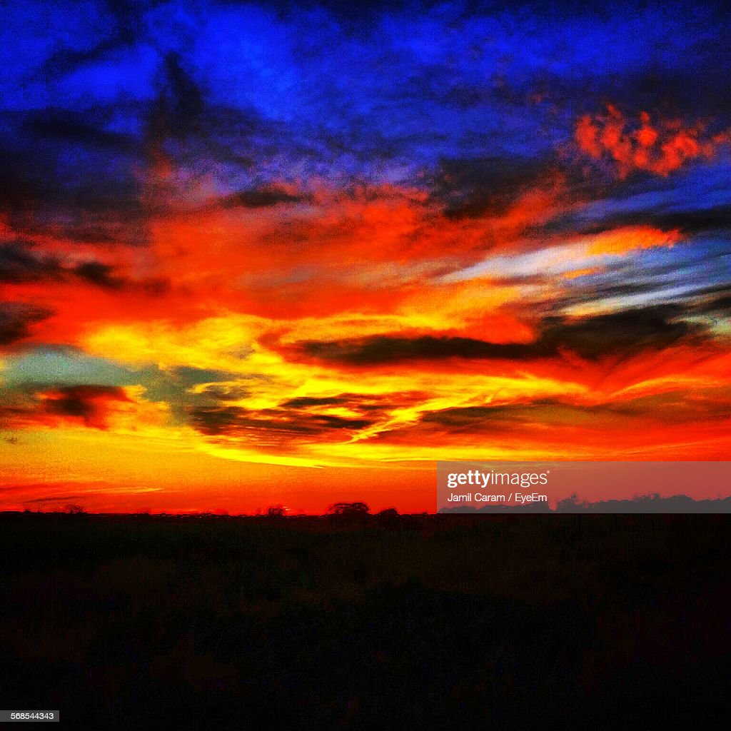 Scenic View Of Dramatic Sky Over Silhouette Field : Stock Photo