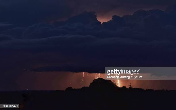 scenic view of dramatic sky over silhouette field - anfang stock pictures, royalty-free photos & images